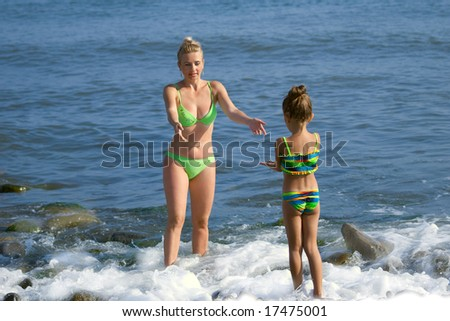 Mother and  daughter a standing in a sea  and extend each other hands