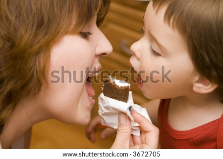Mother and daughter about to bite a candy bar - stock photo