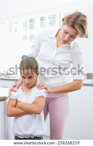Mother and daughter after an argument at home in kitchen - stock photo