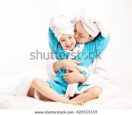 mother and daughter after shower in bed at home - stock photo