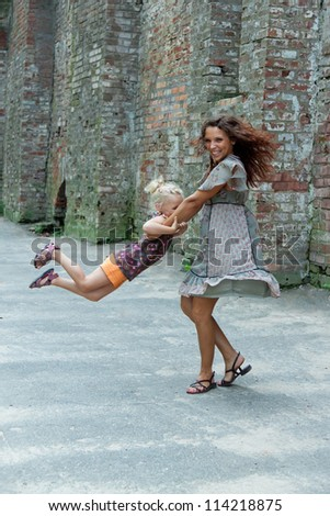 Mother and daughter against a brick wall