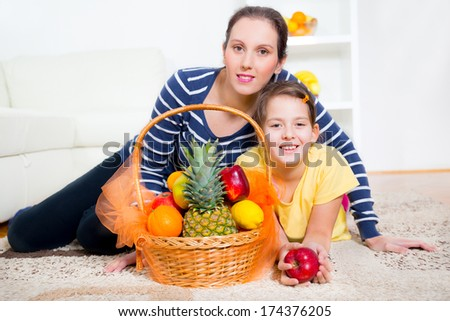 mother and daughter and fruit basket - stock photo