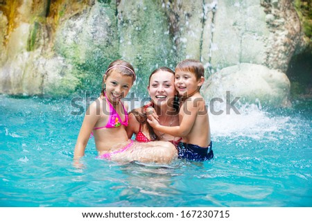 Mother and daughter and son at swimming pool smiling - stock photo