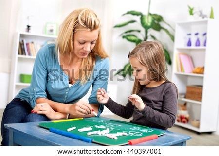 Mother and daughter are drawing on the drawing board - stock photo
