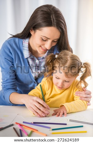 Mother and daughter are having fun while drawing at home. - stock photo