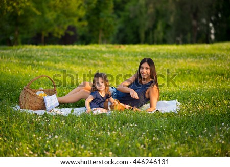 Mother and daughter are having picnic on a blanket and resting in park on a beautiful day