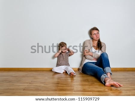Mother and daughter are in quarrel, sitting on the floor and looking sideway - stock photo