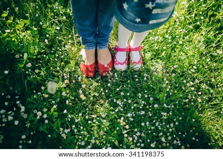 Mother And Daughter Are On The Grass On Summer. Feet Close-up - stock photo