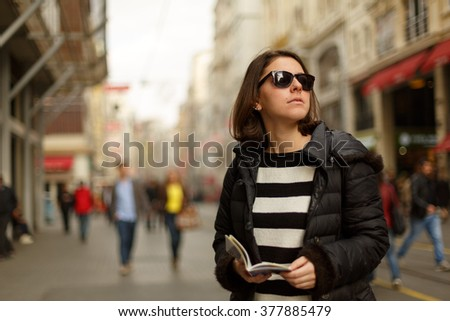Mother and daughter are on the street and looking for a place to visit ,they are using a travel guide to explore where they travel - stock photo