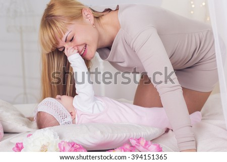 Mother and daughter are playing on bed  - stock photo