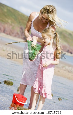 Mother and daughter at beach fishing and smiling - stock photo