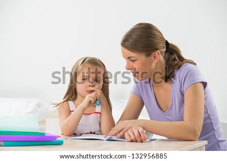 Mother and daughter at home. Mom teaching little girl to draw and write