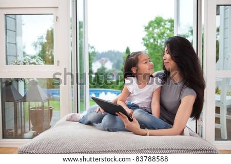 Mother and daughter at home with digital tablet, smiling at eachother