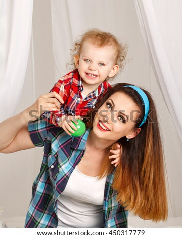 Mother and daughter at home. Young mother and baby daughter hugging and playing ball. Girls dressed in plaid shirt. Mother carry piggyback daughter. Family time - stock photo