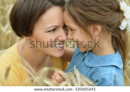 Mother and daughter at summer rye field - stock photo