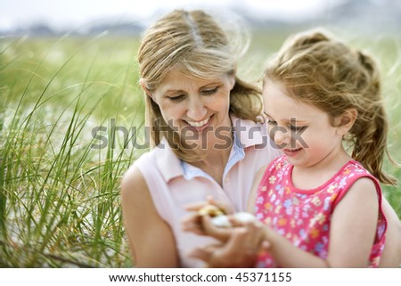 Mother and daughter at the beach look at shells the daughter is holding. Horizontal shot. - stock photo