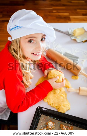 Mother and daughter baking Christmas cookies at home in domestic kitchen  - stock photo