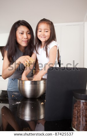 Mother and daughter baking cookies, following a recipe on a digital tablet - stock photo