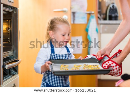 Mother and daughter baking cookies in the oven at home - stock photo