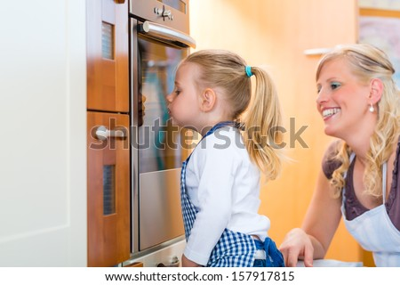 Mother and daughter baking cookies or cooking in the oven at home - stock photo