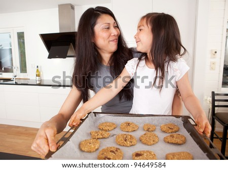 Mother and daughter baking cookies together, holding tray of raw cookie dough - stock photo