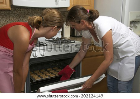 Mother and daughter baking cookies together, taking cookies out of the oven, red hot pad on moms hand pulling cookie sheet out of hot oven. Light brown kitchen cabinets white stove oven - stock photo