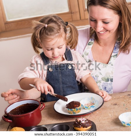 mother and daughter baking cupcakes - stock photo