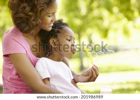 Mother and daughter blowing bubbles - stock photo