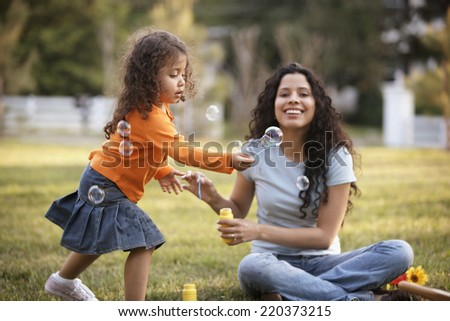 Mother and daughter blowing bubbles outdoors - stock photo