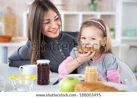 Mother and daughter breakfast in the kitchen. Cute little girl eats bread with peanut butter. - stock photo