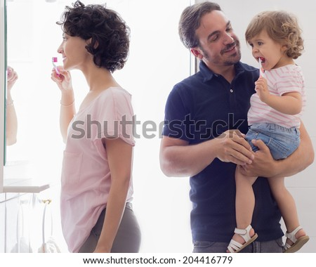 Mother and daughter brush their teeth while the father hold his little girl. - stock photo