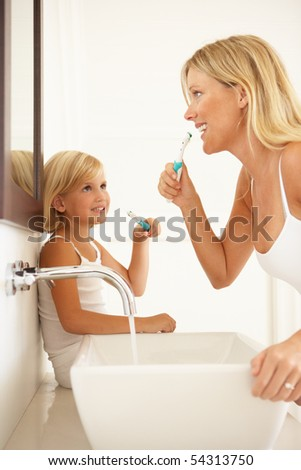 Mother And Daughter Brushing Teeth In Bathroom Together - stock photo