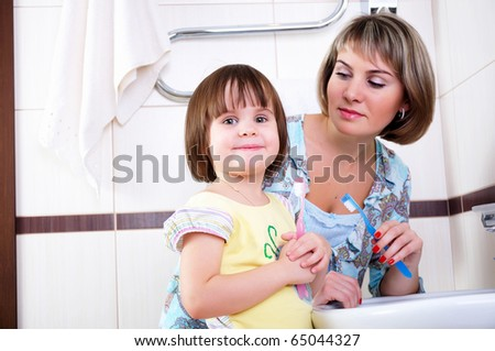 Mother and daughter brushing their teeth together in a bathroom - stock photo