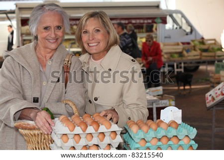Mother and daughter buying eggs at a market - stock photo