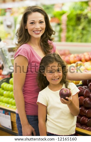 Mother and daughter buying fresh fruit in supermarket