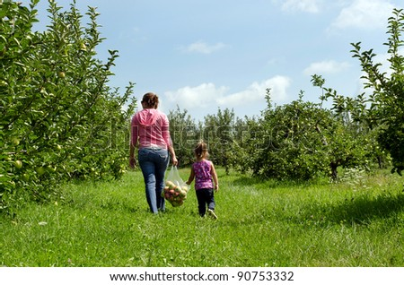 mother and daughter carrying a bag of apples - stock photo