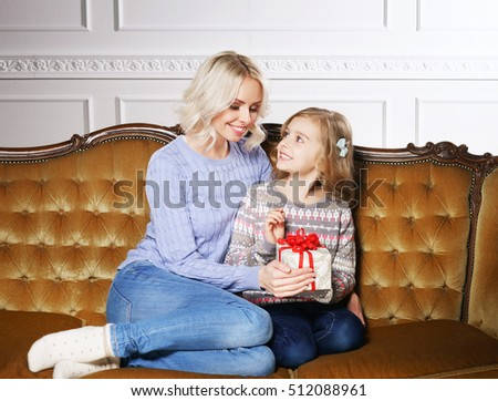 Mother and daughter celebrating Christmas at home. Family with holiday gifts.