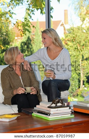 Mother and daughter chatting at home - stock photo
