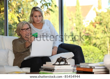 Mother and daughter checking social security online - stock photo