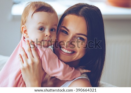 Mother and daughter. Cheerful beautiful young woman holding baby girl in her hands and looking at camera with smile while sitting on the couch at home - stock photo