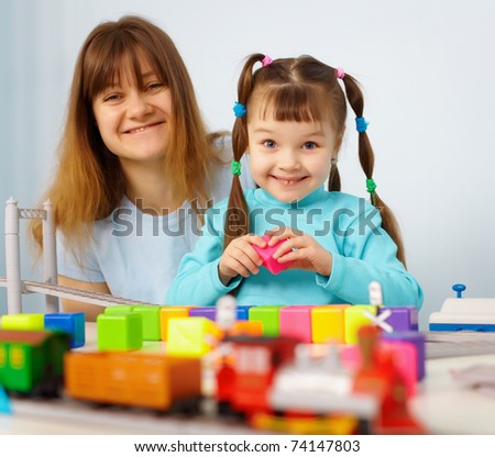 Mother and daughter cheerfully playing with toys on blue - stock photo
