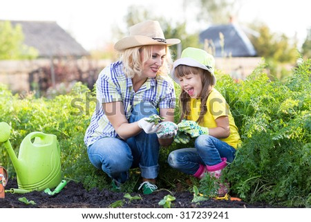 Mother and daughter child planting strawberry seedlings in summer time - stock photo