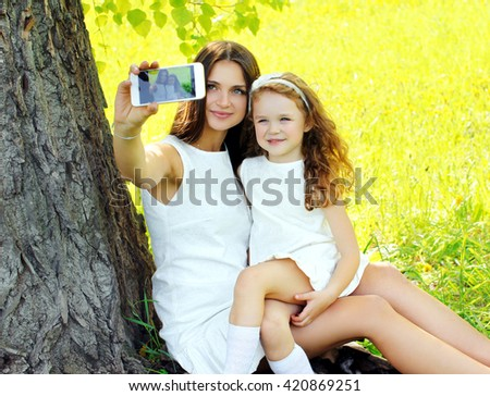 Mother and daughter child taking selfie portrait on smartphone outdoors summer - stock photo