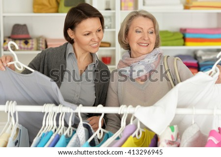 mother and daughter choose things in store and smiling - stock photo