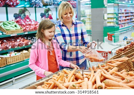 Mother and daughter chooses carrot in the supermarket - stock photo