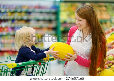 Mother and daughter choosing a melon in a fruit store
