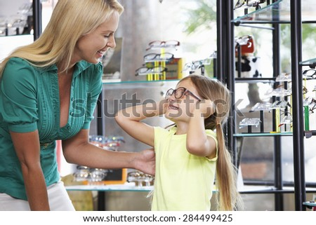 Mother And Daughter Choosing Glasses In Opticians - stock photo