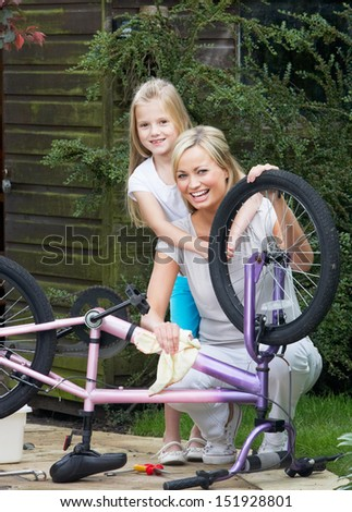 Mother And Daughter Cleaning Bike Together