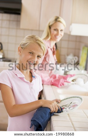 Mother And Daughter Cleaning Dishes - stock photo