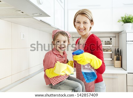 Mother and daughter cleaning in the kitchen - stock photo